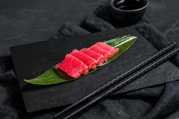 Frischer roher sashimi-thunfisch auf einem steinbrett. draufsicht