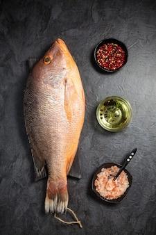 Frischer roher schnapperfisch mit rotem pfeffer, olivenöl und himalaya-steinsalz