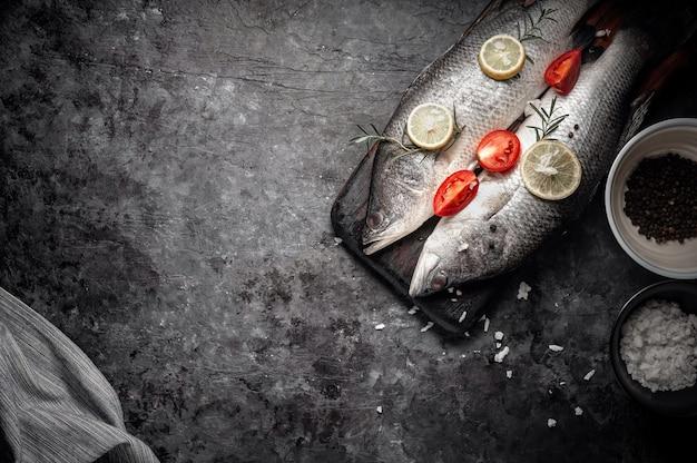 Frischer roher seebarschfisch auf dem hölzernen schneidebrett, konzept kochend.