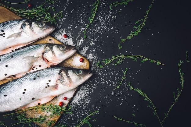 Frischer roher wolfsbarschfisch mit gewürzen, salz, zitrone und thymian auf a