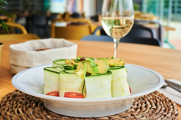 Frischer roher zucchinisalat mit tomaten und avocado, begleitet von einem glas weißwein und einem stoffkorb mit brot mit einem unkonzentrierten restauranthintergrund