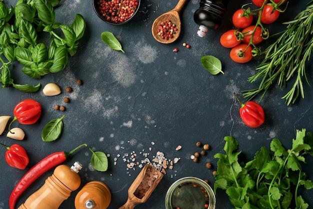 Frischer rosmarin, koriander, basilikum, kirschtomaten, paprika und olivenöl, gewürze, kräuter und gemüse am schwarzen schiefertisch.