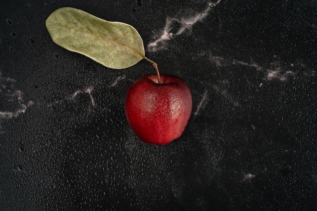 Frischer roter apfel mit grünem blatt und wassertropfen liegt auf einem schwarzen marmorhintergrund voll von wasserspraytröpfchen. draufsicht flach legen zusammensetzung.