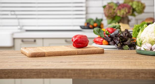 Frischer roter paprika auf einem hölzernen brett vor dem hintergrund eines kücheninnenraums.