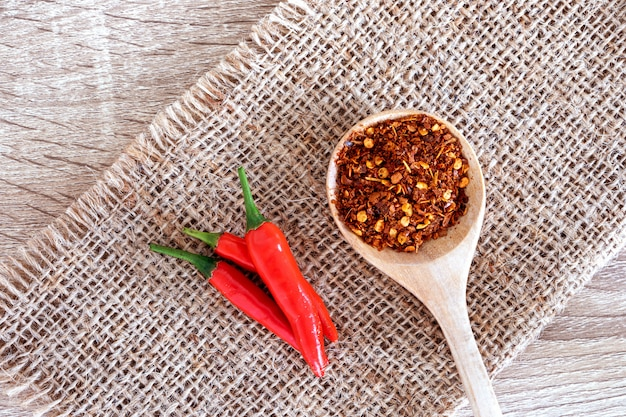 Frischer roter paprikapfeffer und zerstoßener getrockneter roter cayennepfefferpfeffer mit den samen, reich an antioxidativem kräuterfutter