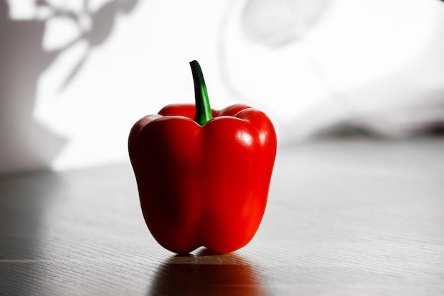 Frischer roter pfeffer auf einem tisch mit sonnenlicht vom küchenfenster