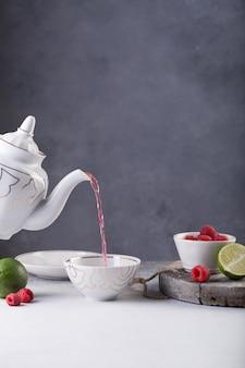 Frischer roter tee wird in eine tasse mit himbeeren und limette auf dem tisch gegossen