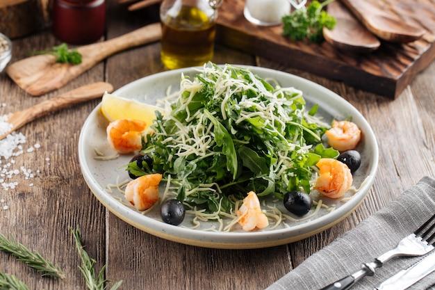 Frischer rucola-salat mit garnelen und oliven