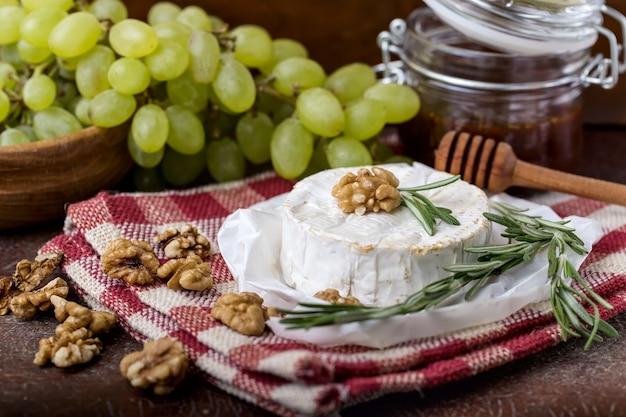 Frischer runder käse auf leinenserviette in weiß-rotem käfig, dose senfhonig, zweig grüner trauben in schüssel aus naturholz, feigenscheibe, rosmarin