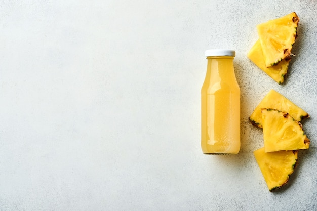 Frischer saft ananas auf glas mit eis und vielfalt in scheiben geschnitten reife tropische früchte grapefruit, orange, limette, zitrone, flache zusammensetzung, auf hellgrauem steinhintergrund.