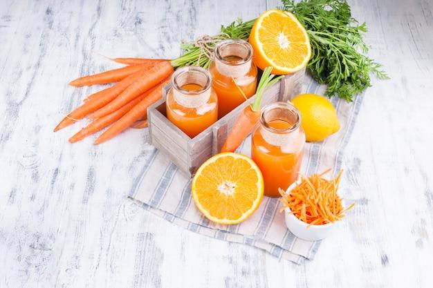 Frischer saft aus karotten, orange und zitrone. karotten mit blättern und anderen frischen früchten auf einem hölzernen hintergrund.