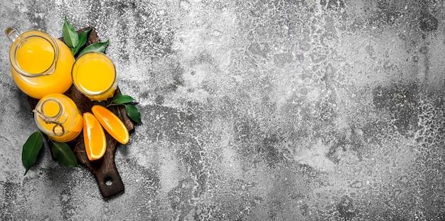 Frischer saft aus reifen orangen. auf rustikalem hintergrund.