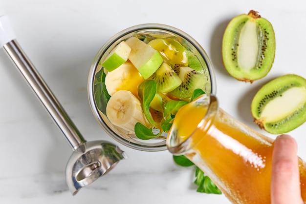Frischer saft, der in einen mixerbehälter mit rohen früchten gießt, um einen gesunden frühstücks-smoothie zuzubereiten, draufsicht