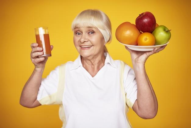 Frischer saft orangen und äpfel sportliche alte dame