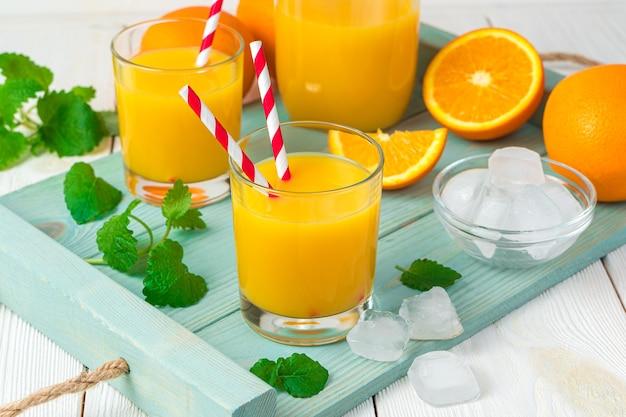Frischer saft und orangen mit minze und eiswürfeln auf einem hellen schreibtisch.