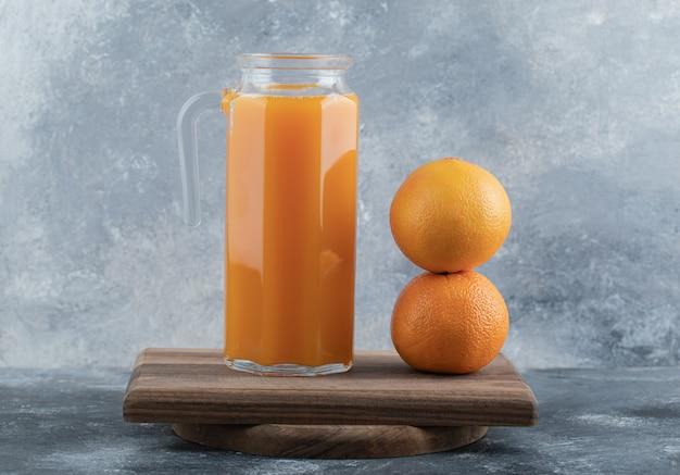 Frischer saft und zwei orangen auf holzbrett.