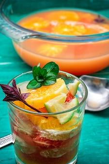 Frischer saft von orangen, kiwi und pampelmuse auf hölzernem hintergrund des türkises.