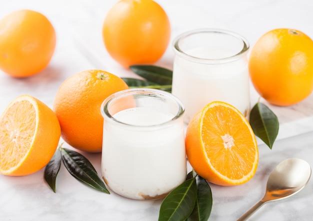 Frischer sahnenachtischjoghurt mit rohen orangen auf hölzernem brett