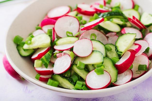 Frischer salat aus gurken, radieschen und frühlingszwiebeln.