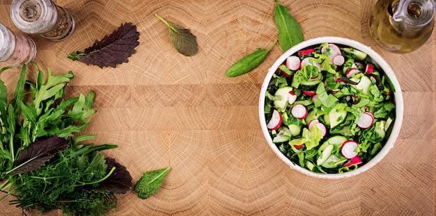 Frischer salat aus gurken, radieschen und kräutern. flach liegen. draufsicht