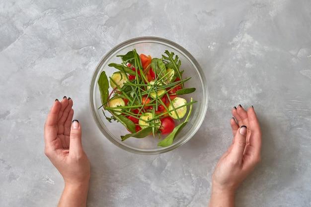 Frischer salat aus rohem gemüse. weibliche hände nehmen einen teller mit einem salat