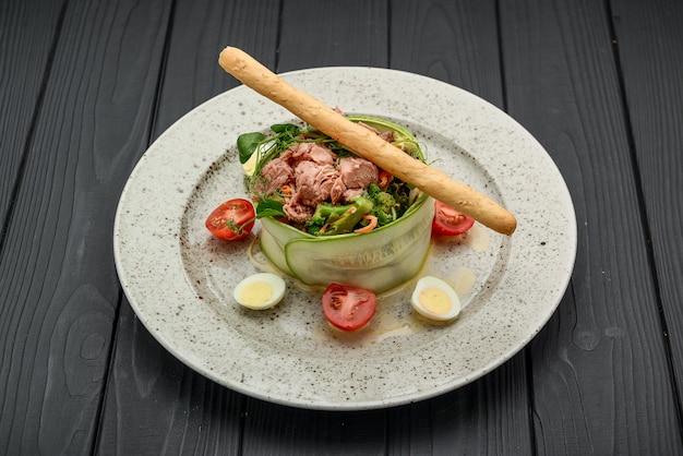 Frischer salat aus thunfisch, gurke, wachteleiern und gemüse auf schwarz