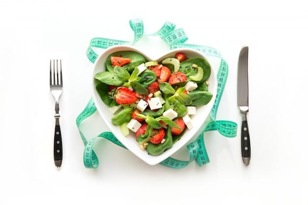 Frischer salat der erdbeere, des selleries, des spinats, des käses in der platte als herz auf weiß.
