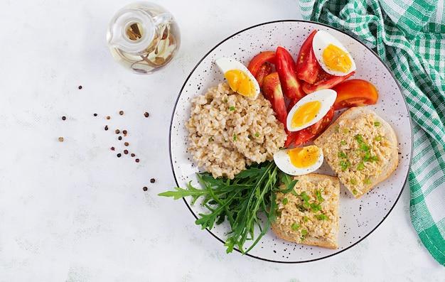 Frischer salat. frühstücksschüssel mit haferflocken, sandwiches mit hühnchen-rillettes, tomate und gekochtem ei. gesundes essen. ansicht von oben, flach