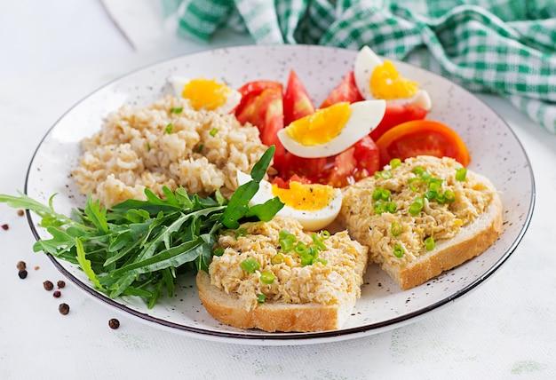 Frischer salat. frühstücksschüssel mit haferflocken, sandwiches mit hühnchen-rillettes, tomate und gekochtem ei. gesundes essen.