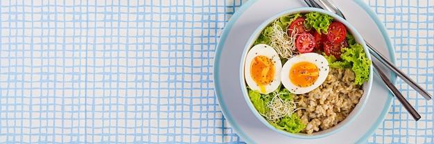 Frischer salat. frühstücksschüssel mit haferflocken, tomaten, salat, microgreens und gekochtem ei. gesundes essen. vegetarische buddha-schüssel. draufsicht, flach liegen