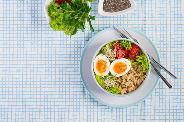 Frischer salat. frühstücksschüssel mit haferflocken, tomaten, salat, microgreens und gekochtem ei. gesundes essen.