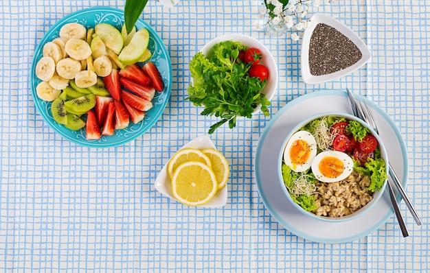 Frischer salat. frühstücksschüssel mit haferflocken, tomaten, salat, microgreens und gekochtem ei.