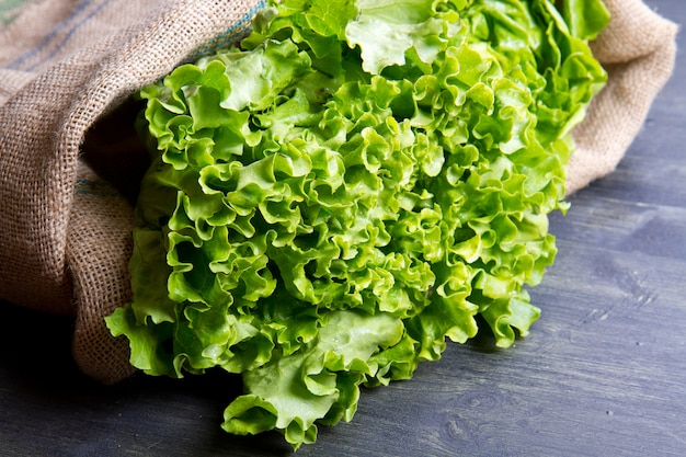 Frischer salat im leinwandsack auf holz