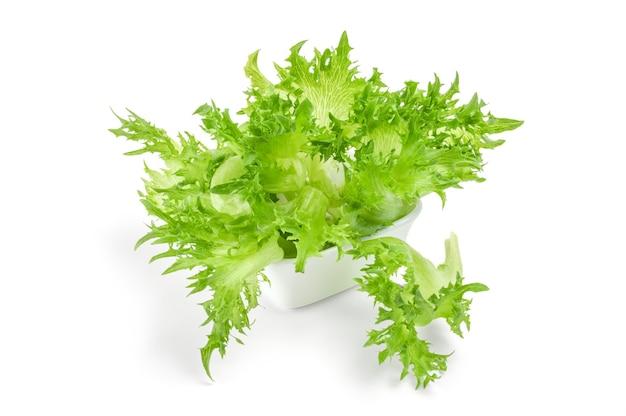 Frischer salat in schüssel auf weißem oberflächenausschnitt isoliert.