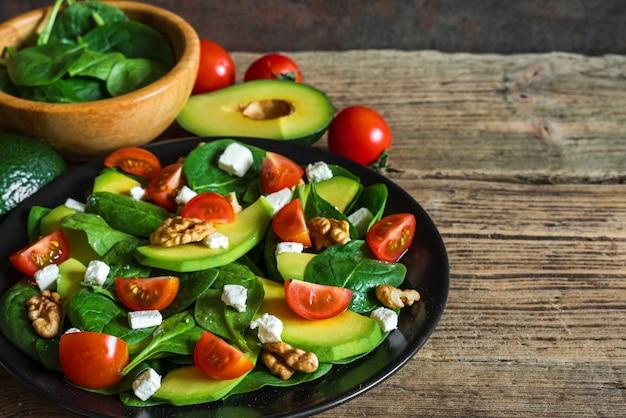 Frischer salat mit avocado, spinat, tomatenkirsche, feta-käse und walnüssen in einem teller auf rustikalem holztisch.