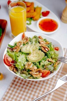Frischer salat mit avocado und walnüssen auf dem tisch