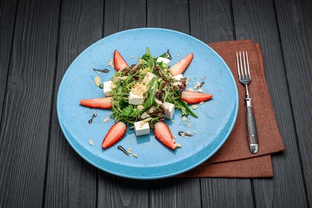 Frischer salat mit erdbeeren, spinatblättern und feta auf altem hölzernem hintergrund