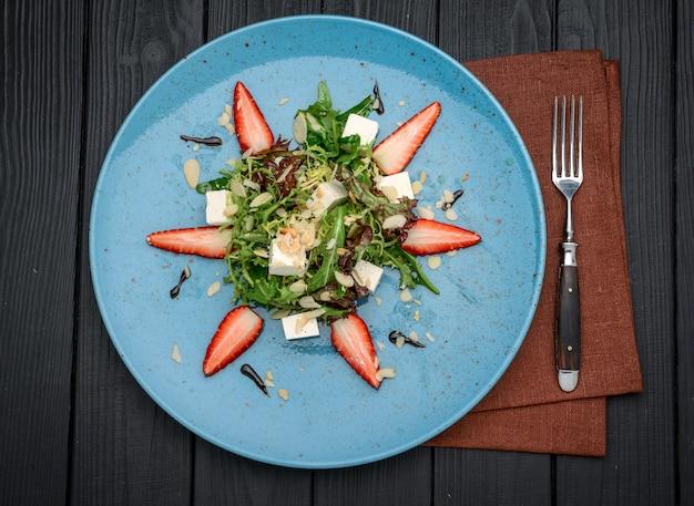 Frischer salat mit erdbeeren, spinatblättern und feta auf altem hölzernem