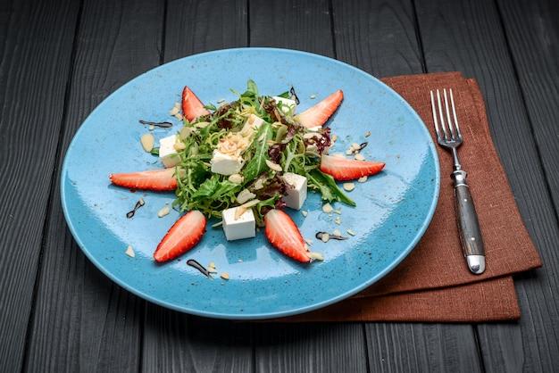 Frischer salat mit erdbeeren, spinatblättern und feta-käse auf altem holzhintergrund