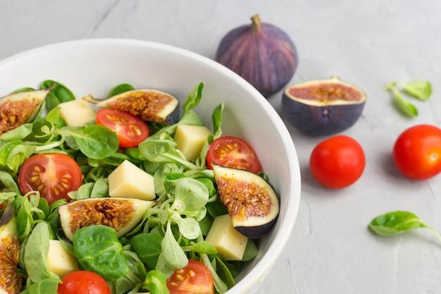 Frischer salat mit feigen, grünen blättern, kirschtomaten und käse auf grau