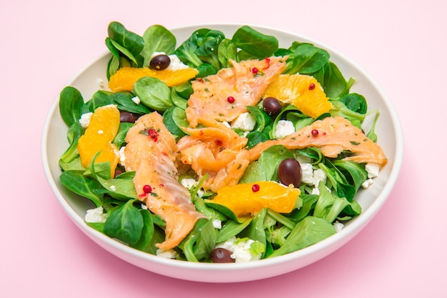 Frischer salat mit geschnittenem mariniertem lachs und orangenfrüchten