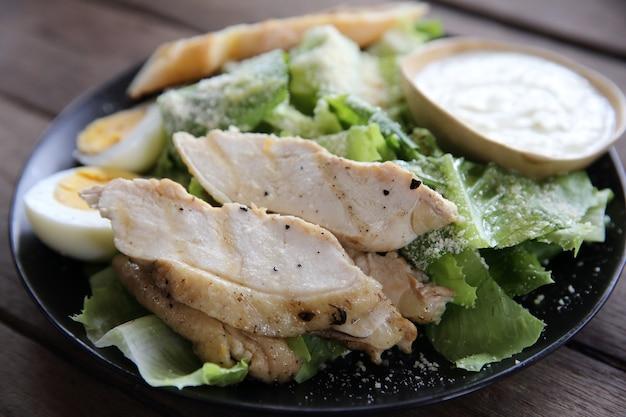Frischer salat mit hähnchenbrust auf holzhintergrund