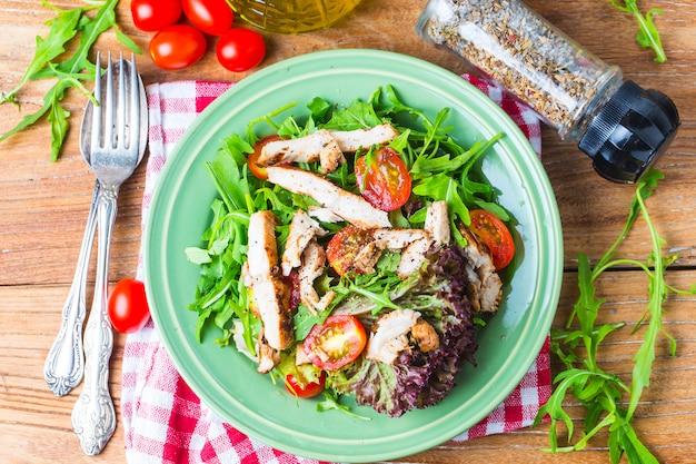 Frischer salat mit hähnchenbrust, rucola und tomate. draufsicht