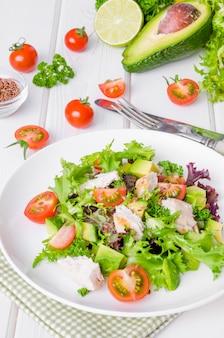 Frischer salat mit huhn, avocado, tomaten und leinsamen auf einer platte auf weißem hölzernem hintergrund. gesundes essen.