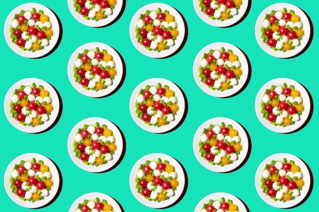 Frischer salat mit kirschtomaten, mozzarella und microgreens. muster von einer platte auf einem grünen hintergrund. draufsicht. kreatives lebensmittelkonzept.