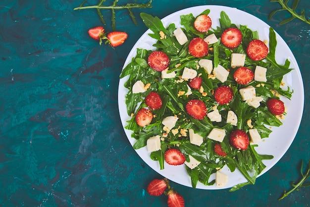 Frischer salat mit rucola, erdbeeren, feta und nüssen