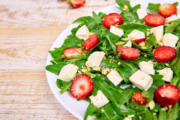 Frischer salat mit rucola, erdbeeren, feta und nüssen.
