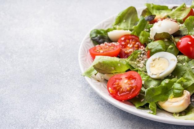 Frischer salat mit tomaten und wachteleiern und salat. platz kopieren