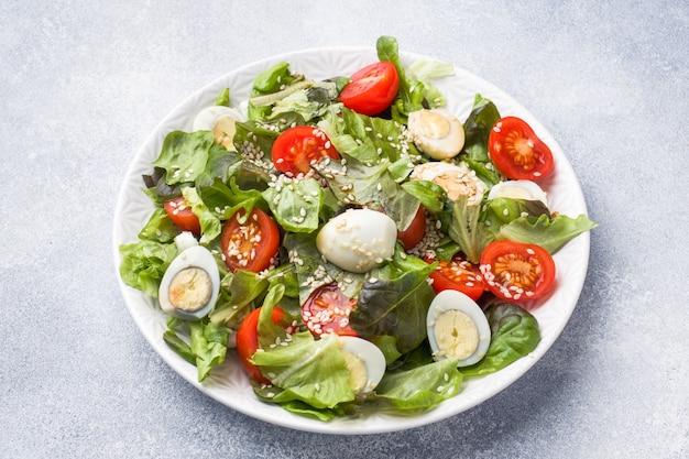 Frischer salat mit tomaten und wachteleiern und salat.