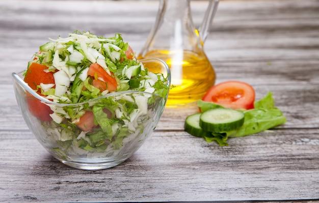 Frischer salat und pflanzenöl stehen auf einem holztisch